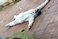 Nhân viên y tế dầm mình trong bộ đồ bảo hộ, làm việc nhiều giờ trong thời tiết nắng nóng gay gắt đã mệt lả nằm ngay xuống sân.
