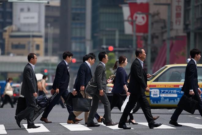 Nhân viên công sở đi bộ đến nơi làm việc ở Tokyo. Ảnh: Japan Times.