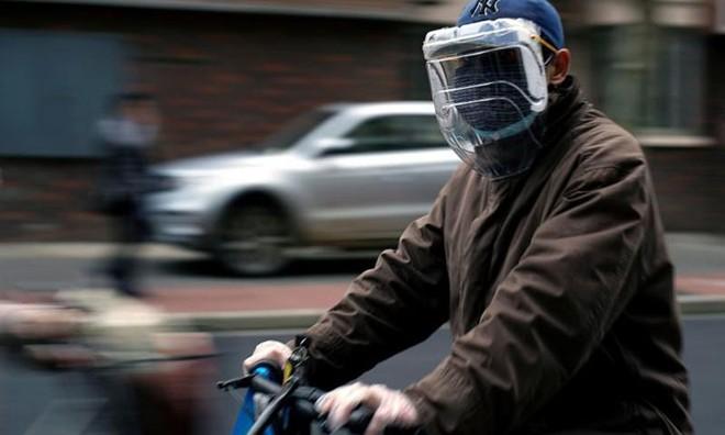 Một người dân đeo khẩu trang và mặt nạ tự chế từ chai nhựa trên đường phố Thượng Hải, Trung Quốc hôm 22/3. Ảnh: Reuters.