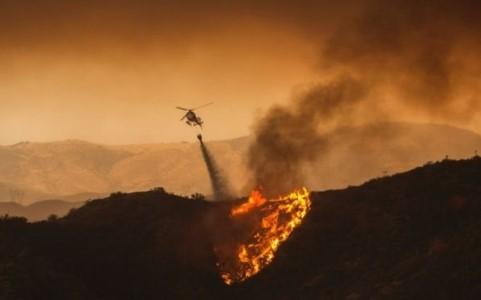 Máy bay trực thăng thả nước dập tắt các đám cháy tại Santa Clarita. Ảnh AFP.