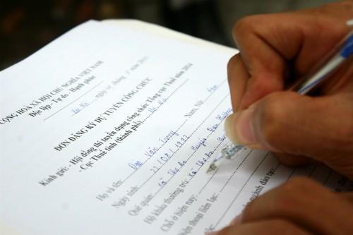 Thí sinh làm đơn đăng ký dự tuyển công chức ngành thuế năm 2014. Ảnh: Bá Đô.