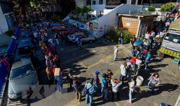 Người dân Venezuela xếp hàng chờ đổi tiền bên ngoài ngân hàng trung ương ở Caracas. (Nguồn: AFP/TTXVN).