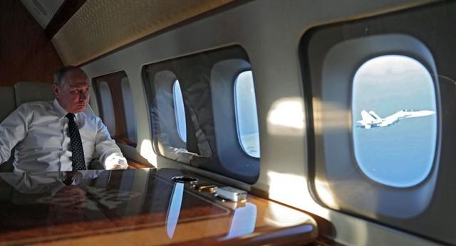 Tổng thống Nga Vladimir Putin ngồi trên chuyên cơ (Ảnh: Sputnik).