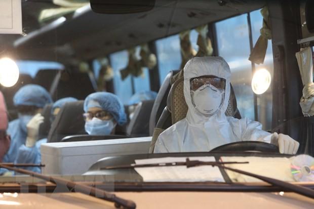 Xe đưa công nhân Việt Nam rời Sân bay Vân Đồn đến khu vực cách ly để điều trị. (Ảnh: Dương Giang/TTXVN).
