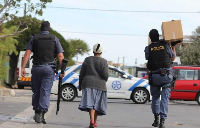 Cảnh sát Nam Phi mang hàng hóa cho một cụ già trên đường đi chợ về. (Ảnh: TTXVN phát).