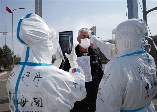 Nhân viên y tế Trung Quốc kiểm tra thân nhiệt ngăn chặn sự lây lan của dịch COVID-19 tại một trạm kiểm tra hải quan ở Suifenhe, tỉnh Hắc Long Giang, gần biên giới với Nga, ngày 1/5/2020. (Ảnh: AFP/TTXVN).
