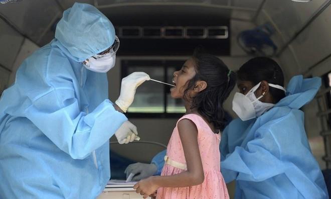 Nhân viên y tế lấy mẫu xét nghiệm nCoV cho một bé gái tại thành phố Chennai, Ấn Độ, hôm 16/6. Ảnh: AFP.