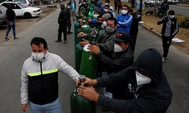 Người dân đeo khẩu trang xếp hàng chờ bên ngoài một cửa hàng phân phối oxy ở thủ đô Lima, Peru hôm 25/6. Ảnh: Reuters.