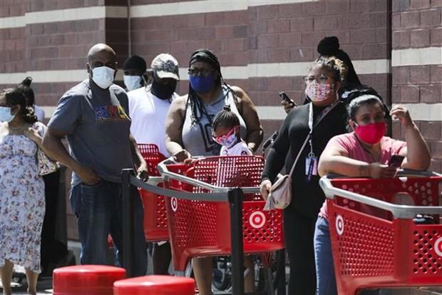 Người dân đeo khẩu trang phòng dịch COVID-19 bên ngoài một siêu thị tại New York, Mỹ. (Ảnh: THX/TTXVN).