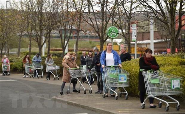 Người dân xếp hàng chờ mua sắm bên ngoài một siêu thị ở Gateshead, Anh. (Ảnh: AFP/TTXVN).
