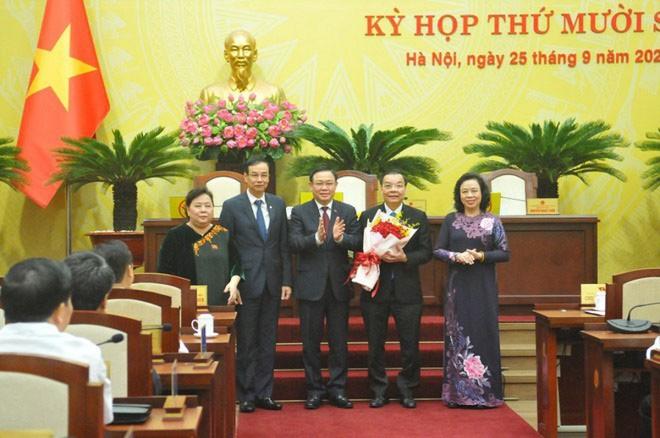 Chủ tịch UBND TP Hà Nội Chu Ngọc Anh nhận hoa chúc mừng từ Bí thư Thành ủy Vương Đình Huệ.