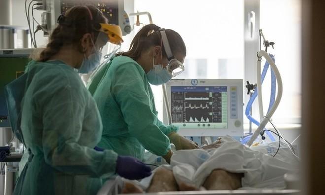Bác sĩ kiểm tra một bệnh nhân Covid-19 tại phòng chăm sóc đặc biệt thuộc Bệnh viện Đại học Torrejon, Tây Ban Nha, ngày 6/10. Ảnh: AP.