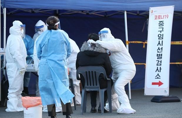 Nhân viên y tế lấy mẫu dịch xét nghiệm COVID-19 cho người dân tại Seoul, Hàn Quốc, ngày 14/12/2020. (Ảnh: THX/TTXVN).