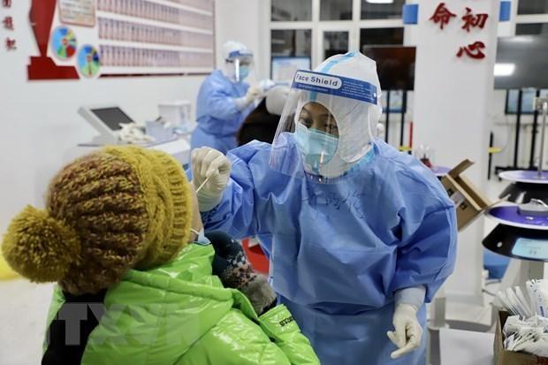 Nhân viên y tế lấy mẫu dịch xét nghiệm COVID-19 cho người dân tại thành phố Tuy Phân Hà, tỉnh Hắc Long Giang, Trung Quốc. (Ảnh: THX/TTXVN)