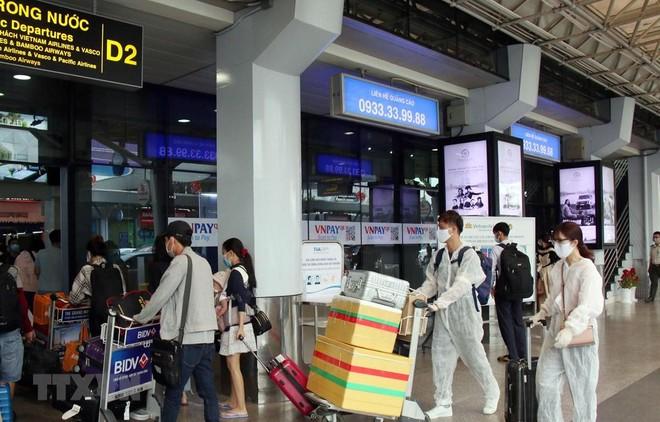 Để phòng chống dịch, nhiều hành khách đã chủ động trang bị các bộ đồ bảo hộ khi đến sân bay Tân Sơn Nhất. (Ảnh: Tiến Lực/TTXVN).
