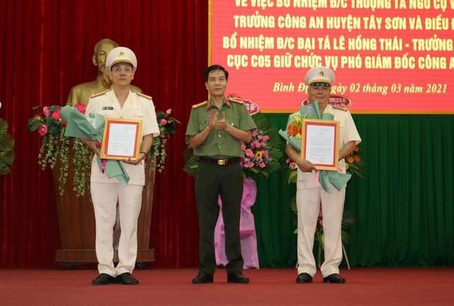 Giám đốc Công an tỉnh Bình Định trao quyết định của Bộ trưởng Bộ Công an cho Thượng tá Ngô Cự Vinh (thứ nhất bên trái sang) và Đại tá Lê Hồng Thái, Trưởng Phòng, Cục C05, Bộ Công an.