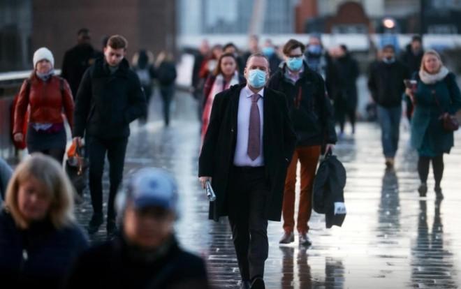 Người dân Anh đi bộ qua cầu London trong đỉnh virus SARS-CoV-2. Ảnh: Reuters.