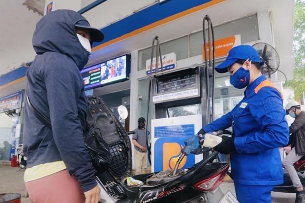 Nhân viên Petrolimex đang bán xăng cho khách hàng. (Ảnh: TTXVN).