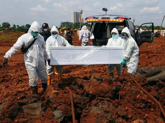 Nhân viên mặc đồ bảo hộ chôn cất nạn nhân Covid-19 tại Jakarta (Ảnh: Reuters).