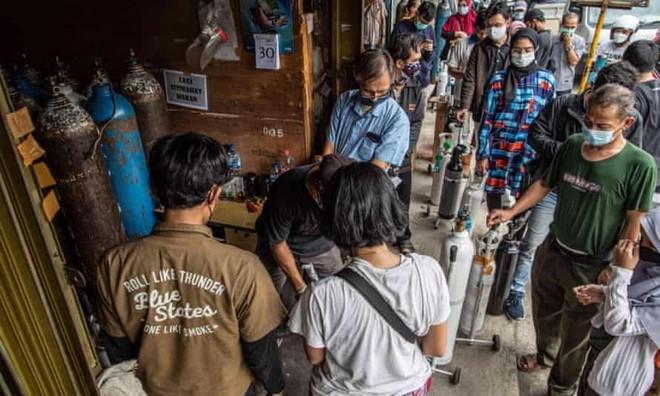Người nhà của bệnh nhân Covid-19 xếp hàng để bơm đầy bình oxy ở Manggarai, Jakarta. Ảnh: Shutterstock.