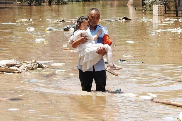Sơ tán trẻ em khỏi khu vực bị ngập do mưa lũ. (Ảnh: AFP/TTXVN).