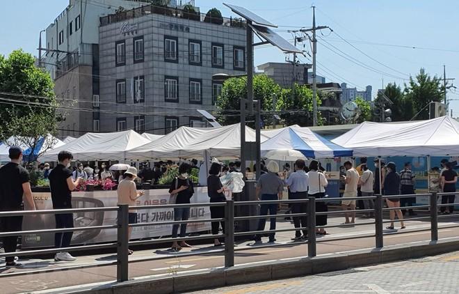 Người dân xếp hàng xét nghiệm COVID-19 trong thời tiết nắng nóng ở quận Seongbuk, Seoul. (Ảnh: Mạnh Hùng/TTXVN).