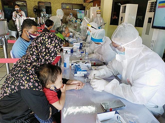 Một người mẹ cho con nhỏ xét nghiệm Covid-19 ở Jakarta, Indonesia (Ảnh: Jakarta Post).