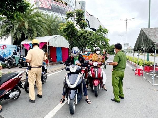 Lực lượng Công an tại chốt kiểm trên đường Phạm Văn Đồng, phường Hiệp Bình Chánh, Thủ Đức, kiểm tra giấy tờ của người lưu thông. (Ảnh: Thành Chung/TTXVN).