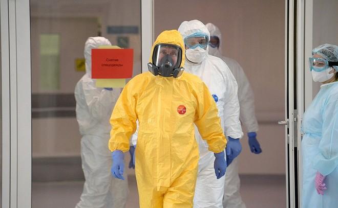 Tổng thống Nga Vladimir Putin (mặc đồ màu vàng) đến thăm khu vực cách ly bệnh nhân nghi nhiễm Covid-19. Ảnh: Kemlin.