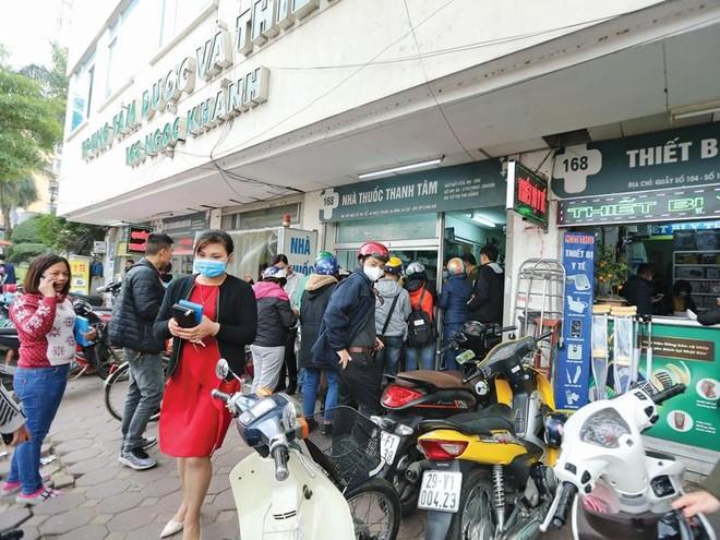 Người dân xếp hàng trước cửa nhà thuốc để chờ mua khẩu trang y tế, dung dịch sát khuẩn... Ảnh: Đức Thanh