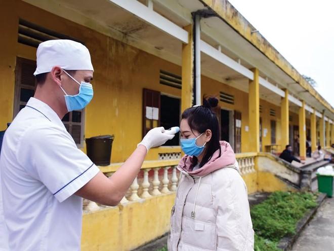 Kiểm tra thân nhiệt người dân trong khu cách ly tập trung tại tỉnh Lào Cai. Ảnh: Giang Huy