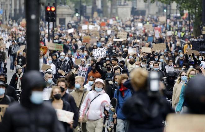 """Các nhà hoạt động cầm biểu ngữ, đeo khẩu trang phòng dịch Covid-19 khi tham gia cuộc tuần hành theo phong trào hoạt động quốc tế """"Black Lives Matter"""" (Người da đen đáng được sống) đến Quảng trường Trafalgar, London vào ngày 12/6/2020. Ảnh tư liệu: AFP"""