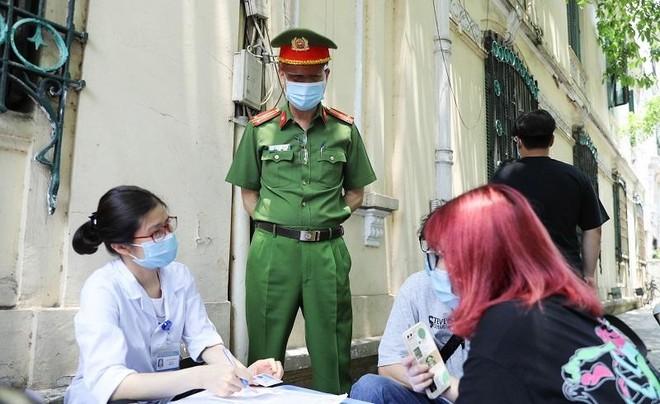Lực lượng chức năng quận Hoàn Kiếm lập biên bản xử phạt người không đeo khẩu trang nơi công cộng.