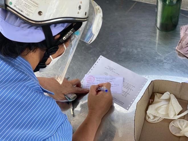 Người dân tại TP.HCM điền thông tin vào thẻ ra vào chợ Bà Chiểu, quận Bình Thạnh (Ảnh: Q.T).