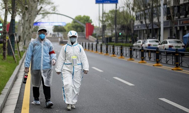 Dân Vũ Hán mặc đồ bảo hộ đi trên phố ngày 31/3. Ảnh: AFP.