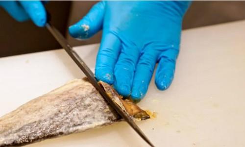 Đầu bếp sau khi lấy cá ra khỏi lớp gạo và muối ướp trước đó thì cắt lát mỏng và đều. Ảnh: Biwako Visitors Bureau.