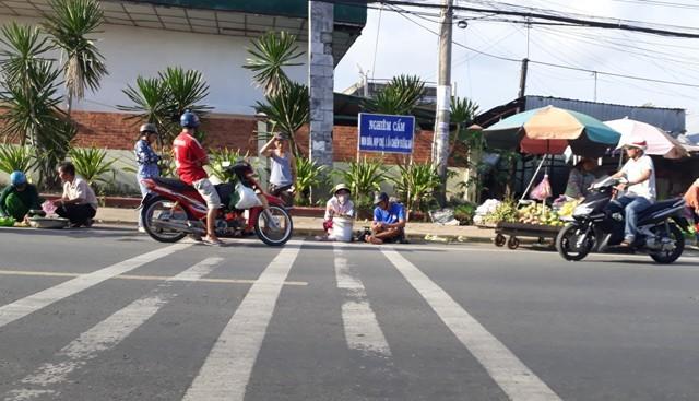 """Dù có bảng cấm nhưng tình trạng chợ mua bán vẫn """"mọc"""" lên ở một số tuyến đường trên địa bàn TP Cà Mau, vi phạm hàng lang an toàn đường bộ. (Ảnh: CTV)."""