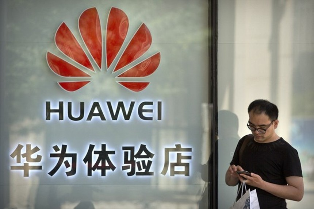 Một người đang sử dụng điện thoại bên ngoài cửa hàng Huawei ở Bắc Kinh. (Nguồn: AP)