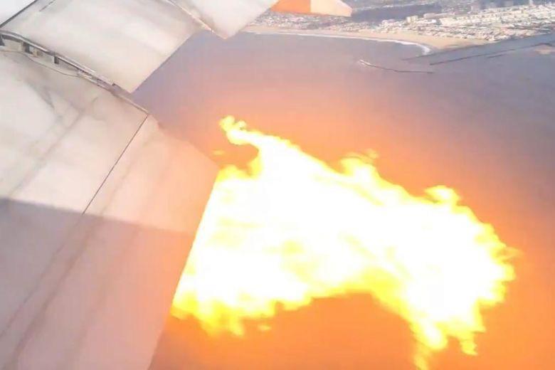 Động cơ chiếc Boeing 777 bị cháy nhìn từ cửa sổ máy bay - Ảnh: REUTERS
