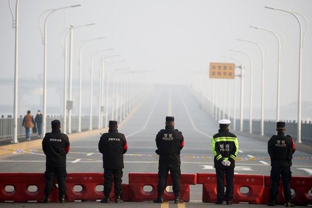Cảnh sát được triển khai canh gác tại trạm kiểm soát trước cây cầu bắc qua sông Trường Giang nối Hồ Bắc với Cửu Giang. (Ảnh: Reuters).