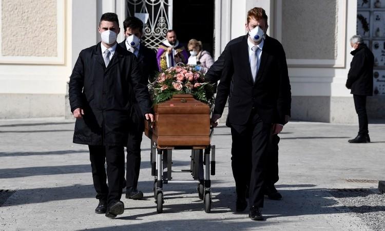 Nhóm người khiêng linh cữu đeo khẩu trang tại đám tang của một phụ nữ chết do nCoV ở Seriate. Italy, hôm 28/3. Ảnh: Reuters.