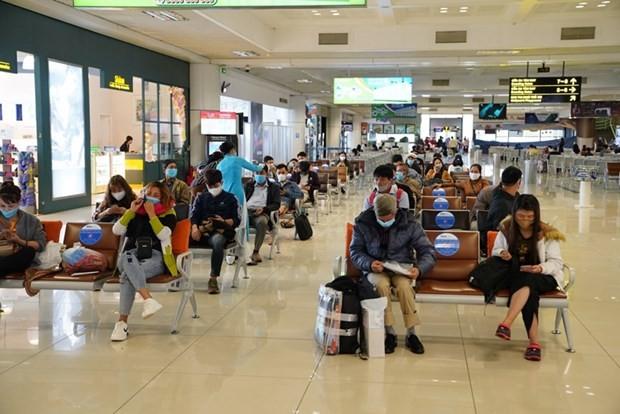 Hành khách tuân thủ giữ khoảng cách khi ngồi tại nhà ga tại sân bay Nội Bài. (Ảnh: Phan Công/Vietnam+).