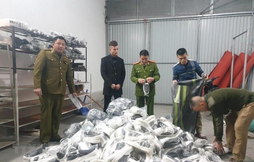 Lực lượng chức năng phát hiện thu giữ các sản phẩm quần áo, giầy dép lậu tại Hải Dương. (Ảnh: TTXVN phát).