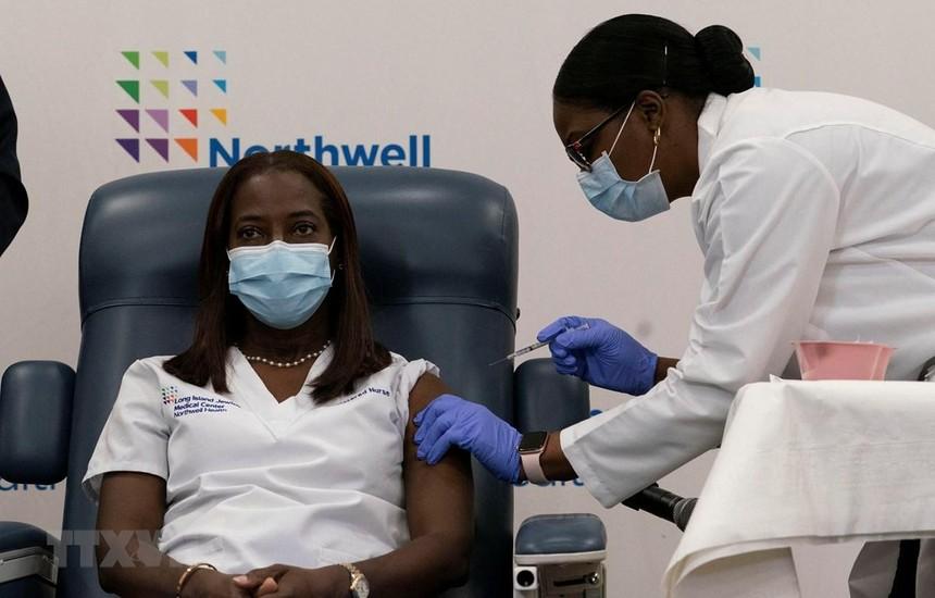 Nhân viên y tế tiêm vắcxin phòng COVID-19 cho người dân tại New York, Mỹ. (Ảnh: AFP/TTXVN).