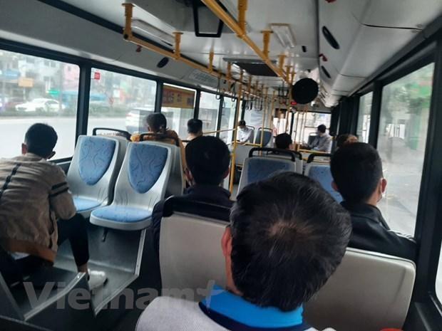 Hành khách đeo khẩu trang và được bố trí ngồi giãn cách theo đúng quy định khi đi xe buýt. (Ảnh: Việt Hùng/Vietnam+).