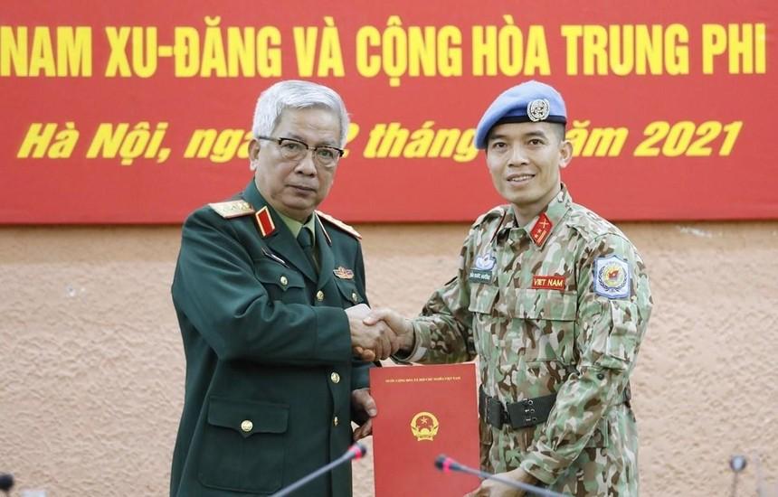 Thượng tướng Nguyễn Chí Vịnh, Thứ trưởng Bộ Quốc phòng trao Quyết định của Chủ tịch nước cho Trung tá Trần Đức Hưởng đi thực hiện nhiệm vụ tại Trụ sở Liên hợp quốc (tại New York, Hoa Kỳ). (Ảnh: Dương Giang/TTXVN).