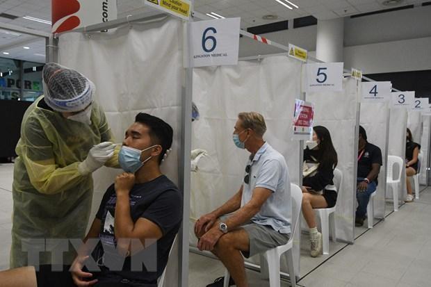 Nhân viên y tế lấy mẫu xét nghiệm COVID-19 cho người dân tại Singapore ngày 27/2/2021. (Ảnh: THX/TTXVN).