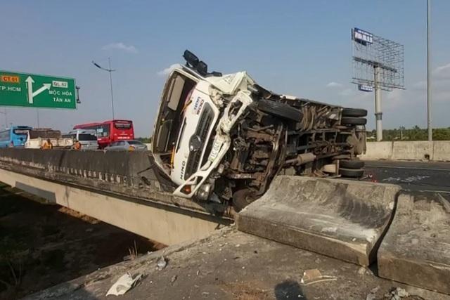 Sau cú tông mạnh của xe khách, xe tải bị lật trên tuyến cao tốc Trung Lương - TPHCM.