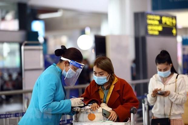 Nhân viên của hãng hàng không hướng dẫn khách làm thủ tục khai báo y tế trước khi vào điểm soi chiếu để lên tàu bay. (Ảnh: Huy Hùng/TTXVN).