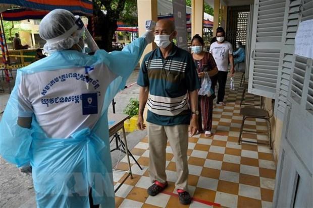 Kiểm tra thân nhiệt phòng lây nhiễm COVID-19 tại Phnom Penh, Campuchia. (Ảnh: AFP/TTXVN).